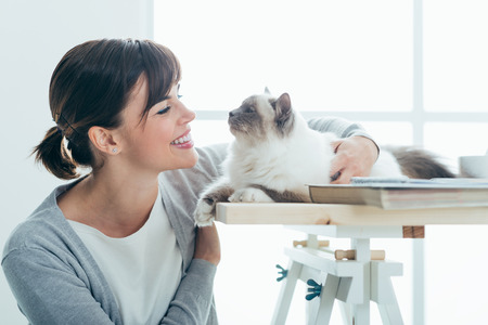 Happy smiling woman at home cuddling and holding her lovely cat on a table, pets and togetherness concept Фото со стока