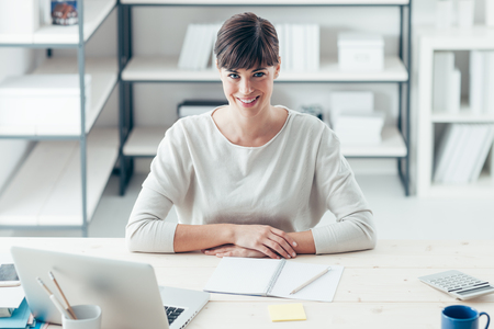 attractive woman: Young confident businesswoman in her office sitting at desk and smiling at camera