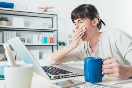Stanco donna sonnolenta sbadigliare, lavorando alla scrivania in ufficio e con una tazza di caffè, superlavoro e dormire concetto di deprivazione