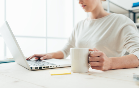 Office women: Young woman at desk networking and connecting to internet using a laptop, she is having a coffee and holding a mug