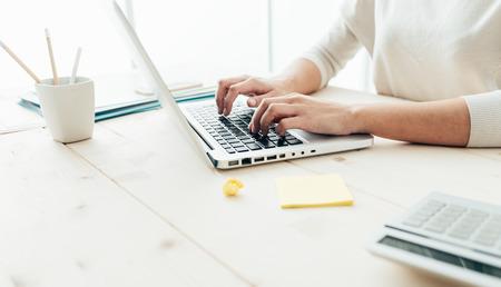trabajando en casa: Mujer que se sienta en el escritorio y de trabajo en manos de ordenador cerca