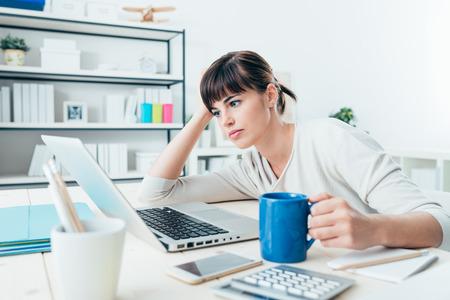 Moe slaperig vrouw werkt op kantoor bureau en met een kopje koffie, overwerk en slaaptekort begrip