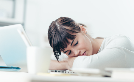 deprivation: Young tired woman at office desk sleeping with eyes closed, sleep deprivation and stressful life concept
