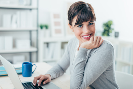 座っている幸せな自信を持っている実業家事務机とノート パソコンでの作業、彼女はカメラに微笑んでいます