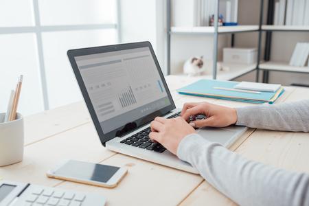 empleado de oficina: De negocios sentado en el escritorio de oficina y escribiendo en un ordenador portátil manos de cerca