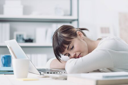 sleepiness: Young tired woman at office desk sleeping with eyes closed, sleep deprivation and stressful life concept