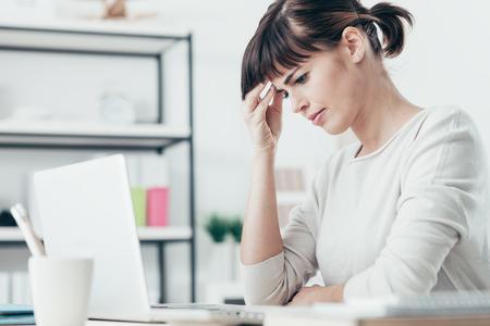 悲しい疲れてひどい頭痛を持つ女性、彼女は事務所の机に座って、彼女の寺に触れる