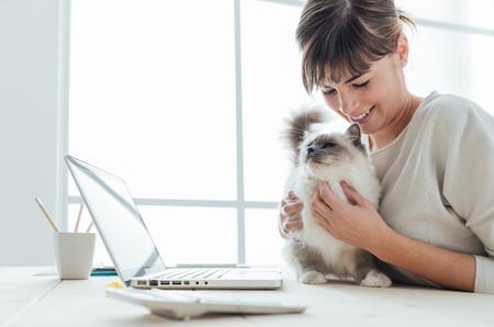 amigos abrazandose: Joven mujer sentada en el escritorio y que abraza a su gato precioso, uni�n y mascotas concepto