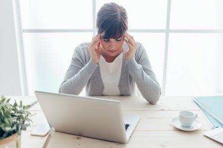mujer joven agotada que trabaja en el escritorio de oficina que toca sus templos, ella está teniendo un fuerte dolor de cabeza, la vida y la enfermedad estresante concepto
