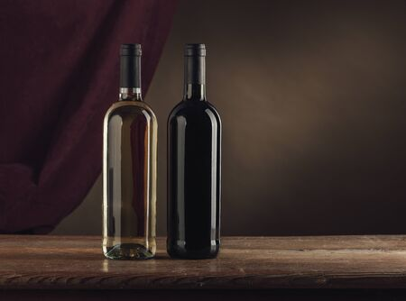 Red and white wine bottles on a rustic wooden table, drape on background, wine tasting still life Archivio Fotografico