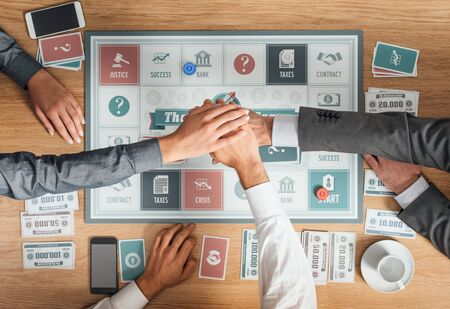 business game: People playing a business board game on a wooden table and stacking hands, cooperation and teamwork concept