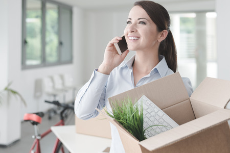 people moving: Beautiful smiling woman moving in a new office, talking on the phone and holding an open cardboard box Stock Photo