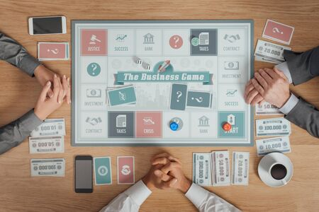 unrecognizable people: People playing a business board game on a wooden table, they are waiting with clasped hands, top view, unrecognizable people Stock Photo
