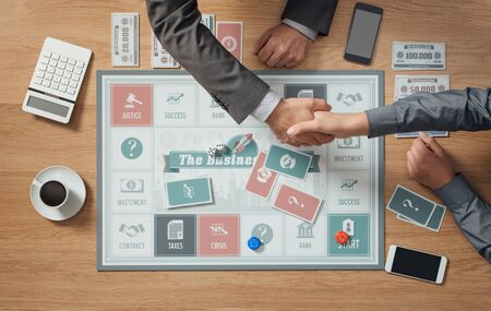 business game: People playing a business board game on a wooden table, hands shaking close up, partnership and agreement concept