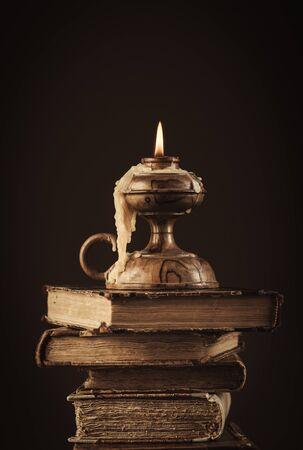 libros antiguos: Pila de libros antiguos y vela encendida en la parte superior, la lectura y el conocimiento concepto