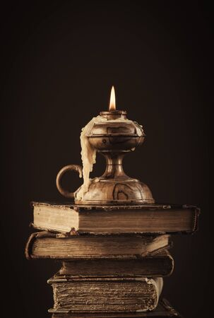 ancient books: Pile of ancient books and lit candle on top, reading and knowledge concept