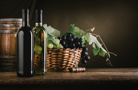 Wine bottles, barrel and grapes in a basket on a wooden table, wine tasting still life Stock Photo