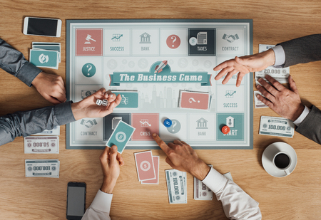business game: People playing a business board game on a wooden table, rolling dices and holding cards, top view Stock Photo