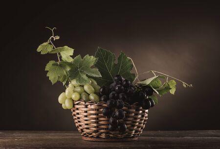 corbeille de fruits: raisins mûrs dans un panier sur une table en bois rustique avec des feuilles de vigne, nature morte classique