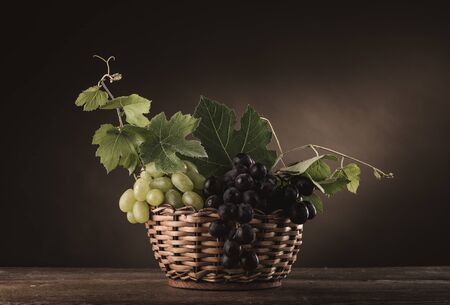 fruit basket: Ripe grapes in a basket on a rustic wooden table with vine leaves, classic still life