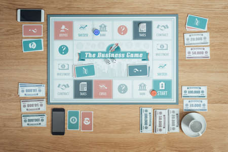 business game: The business board game on a table with pieces, banknotes, cards and players smart phones, business challenge concept