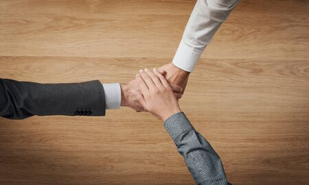 unrecognizable people: Business people stacking hands close up, wooden desktop on background, unrecognizable people