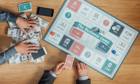 business game: People playing a business board game on a wooden table, one player is holding a lot of money and winning, hands top view Stock Photo