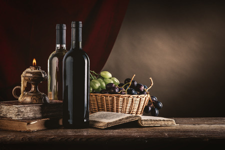antique table: Wine bottles, old books, candle and ripe grapes in a basket on a rustic wooden table, still life