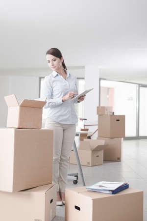 cajas de carton: Empresaria que se mueve en su nueva oficina rodeada de cajas de cartón, que es la celebración de una tableta digital Foto de archivo