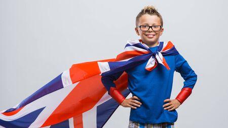 ni�o parado: Divertido sonriente chico s�per h�roe que presenta con los brazos en jarras y llevaba una bandera brit�nica como un cabo
