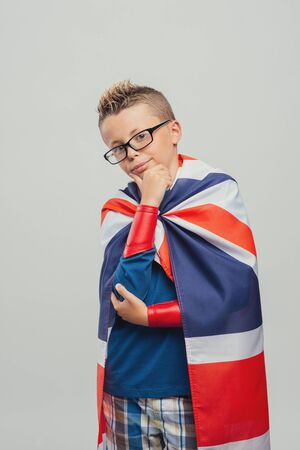 dressing up costume: Cute superhero with hand on chin, looking at camera and wearing a British flag as a cape Stock Photo