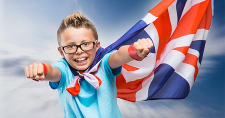 Glimlachend Britse super held het dragen van een vlag als een cape en vliegen met opgeheven vuisten Stockfoto