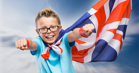 Smiling British super hero wearing a flag as a cape and flying with raised fists Stock Photo - 54081124