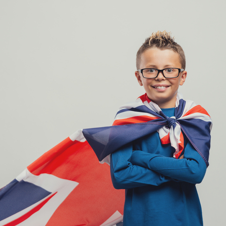 invincible: Smiling superhero boy standing with crossed arms and looking at camera, he is wearing a British flag as a cape Stock Photo