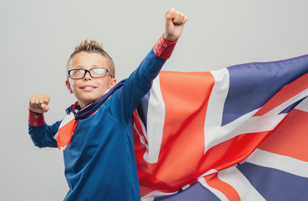 invincible: Cute smiling super hero boy posing with fists raised and wearing a British flag as cape
