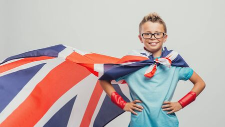 arms akimbo: Cute smiling superhero boy posing with arms akimbo and wearing a British flag as a cape, learning languages concept