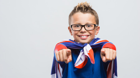 i kids: Funny smiling superhero boy pointing at camera, he is wearing a Union Jack flag as a cape