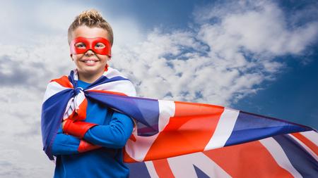かわいい英語スーパー ヒーローのマスクとマントとユニオン ジャックの旗を身に着けている笑みを浮かべて、彼は交差の腕と立っています。
