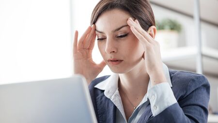 over burdened: Exhausted businesswoman in her office with head in hands, she is having a bad headache, overwork and stress concept