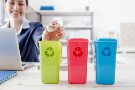 Afval gescheiden inzameling en recycling in de werkplaats, beambte het sorteren van afval met behulp van verschillende vuilnisbakken