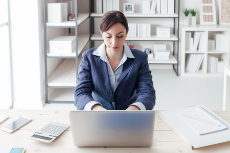 professionalism: Confident young businesswoman working with a laptop in her office, professionalism and efficiency concept