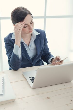woman work: Pensive businesswoman in the office touching her forehead and reading sms on her smart phone