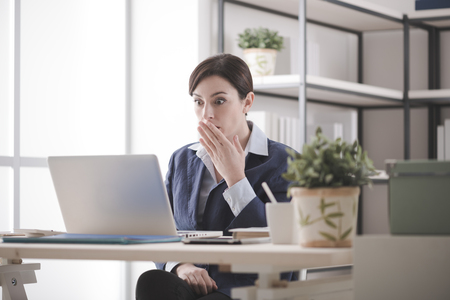 in shock: Young businesswoman having problems with her computer, she is staring shocked at the screen with an hand over mouth Stock Photo