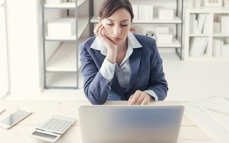 Deprimido de negocios aburrido que trabaja en el escritorio de oficina y trabajo en red con un ordenador portátil, aburrido concepto de trabajo