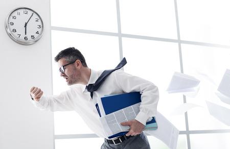 Stressed angstig zakenman in een haast controle tijd en lopen, is hij te laat voor zijn zakelijke afspraak