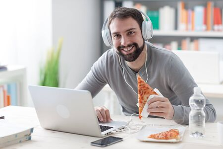 computer office: Young handsome man smiling at camera, using a laptop and eating a slice of pizza Stock Photo