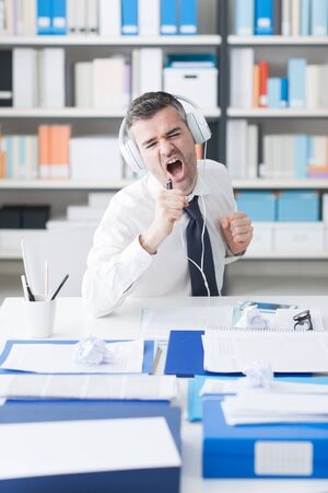 fun at work: Cheerful businessman sitting at office desk, listening to music using headphones and singing, enjoyment and fun concept