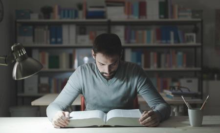 joven seguro studying tarde por la noche, que está sentado en el escritorio y la lectura de un libro, el conocimiento y el aprendizaje de conceptos Foto de archivo