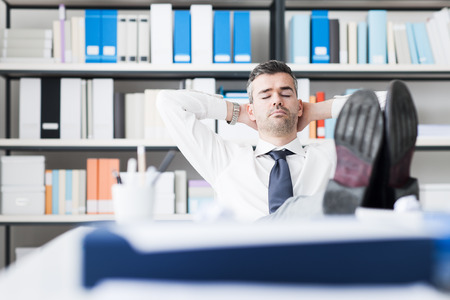 perezoso: Lazy empresario de dormir en la oficina con los pies encima de la mesa y las manos detrás de la cabeza Foto de archivo