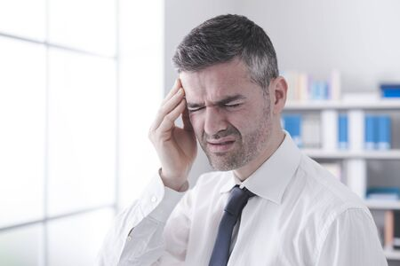 closing eyes: Businessman in his office having a bad headache, he is closing eyes and touching his temple